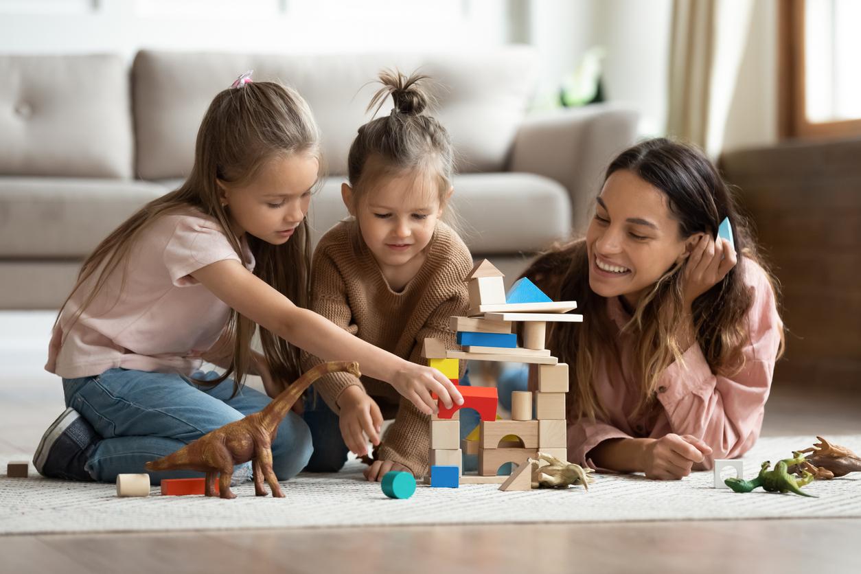 Deux petites filles et maman jouant ensemble jeux bois